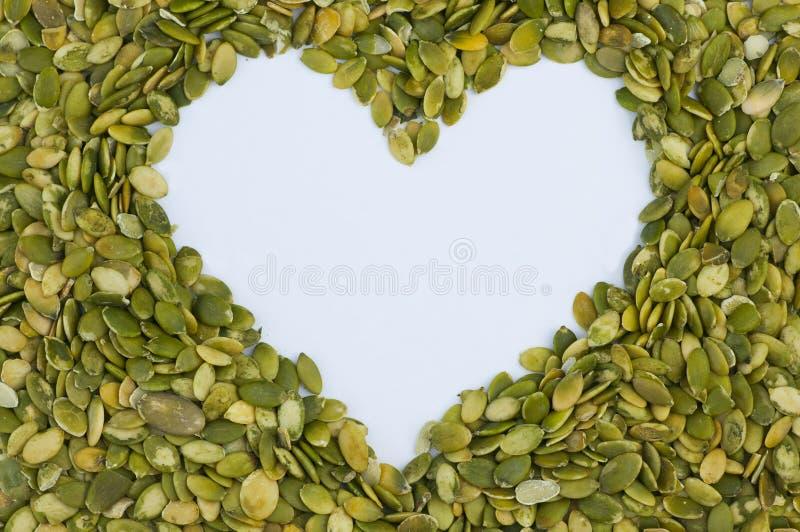 Forma do coração feita das sementes de abóbora descascadas imagem de stock