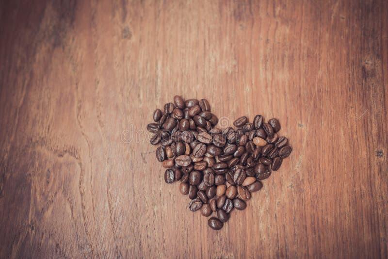 Forma do coração feita dos feijões de café na madeira fotos de stock