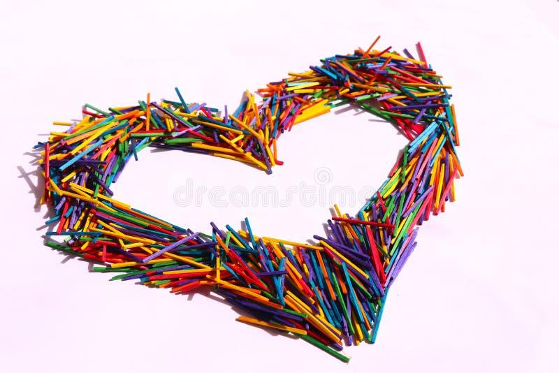 A forma do coração fez de stiks de madeira multicoloridos imagem de stock royalty free