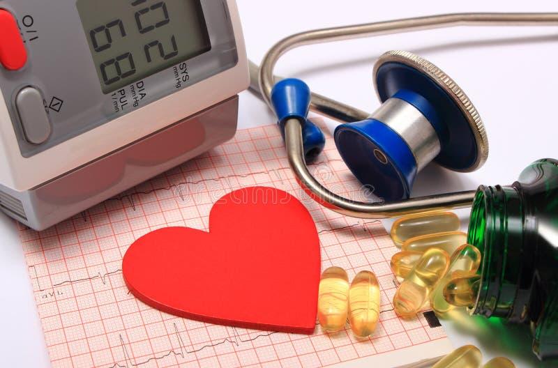 Forma do coração no eletrocardiograma, monitor da pressão sanguínea, estetoscópio fotografia de stock