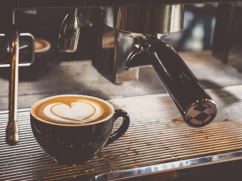 Forma do coração do teste padrão da arte do latte do café com a máquina na cafetaria ou no café foto de stock royalty free
