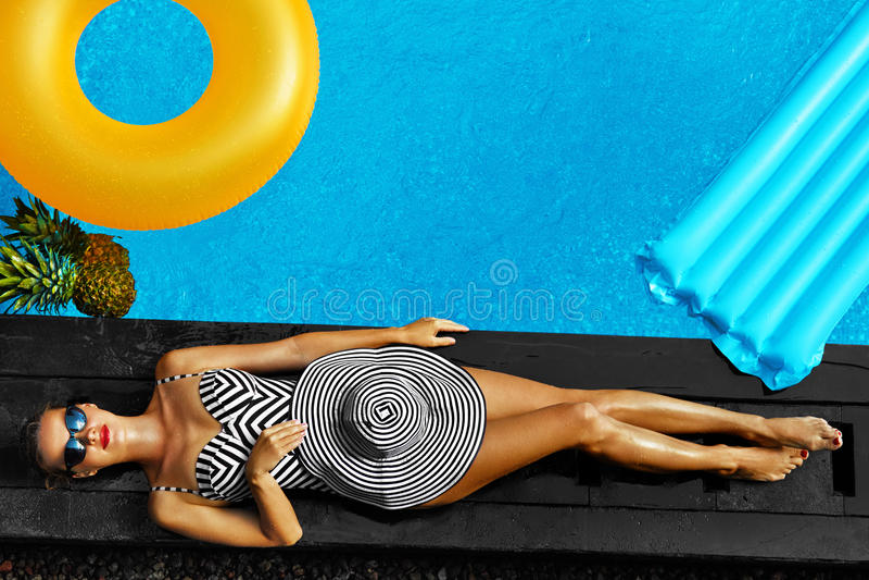 Forma do verão da mulher Banho de sol 'sexy' da menina pela piscina beleza fotografia de stock