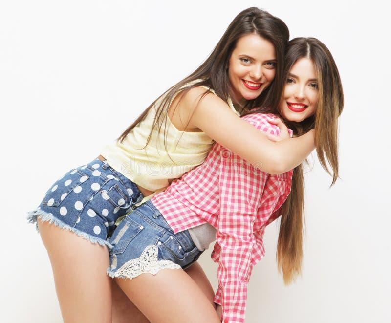 Forma dois que ri as namoradas pintadas que abraçam e que têm o divertimento fotografia de stock royalty free