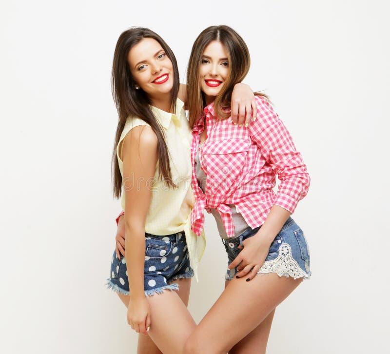 Forma dois que ri as namoradas pintadas que abraçam e que têm o divertimento fotos de stock royalty free