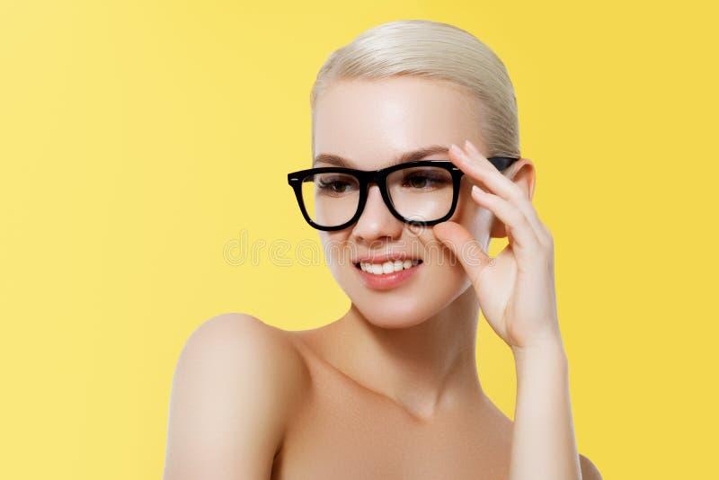 Forma e acess?rios Menina modelo isolada sobre o fundo amarelo Mulher loura à moda da beleza que levanta nos vidros imagem de stock royalty free