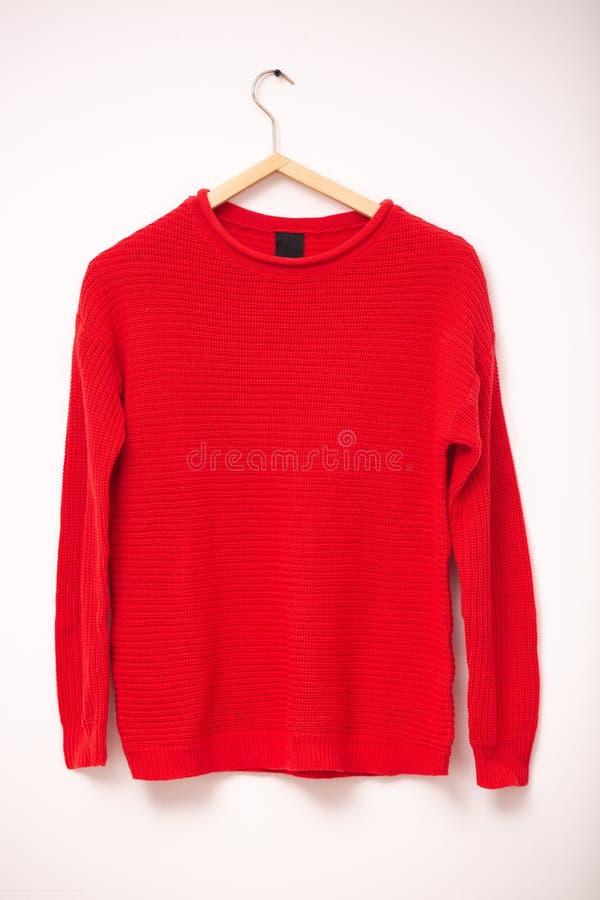 Forma e conceito da roupa Camiseta morna feita malha vermelha da mulher em ganchos contra o fundo branco Tiro vertical foto de stock royalty free
