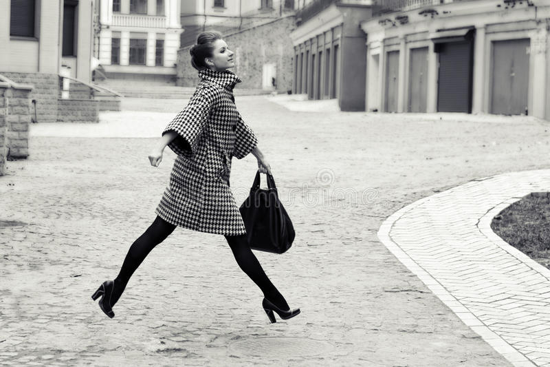 Forma e conceito dos povos - jovem mulher ou adolescente feliz que correm e que saltam altamente na rua da cidade fotografia de stock royalty free