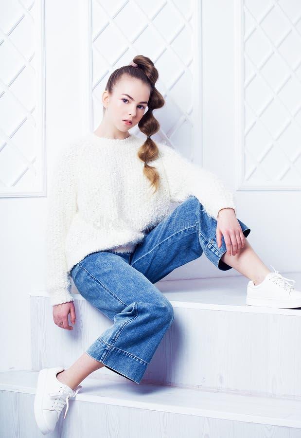 Forma e conceito dos povos: menina adolescente à moda na roupa ocasional que senta-se em escadas e no levantamento fotografia de stock