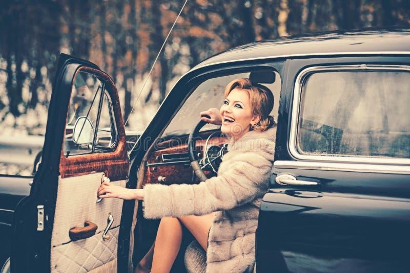 A forma e o estilo retro, modelo de forma no casaco de pele do inverno conduzem o carro retro imagem de stock