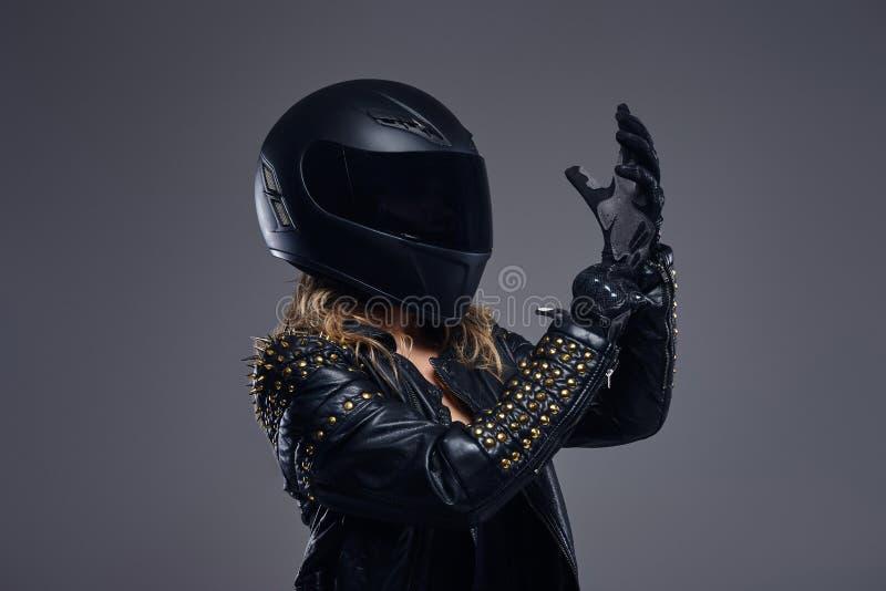 Forma, esporte, extremo Retrato de um traje de couro vestindo do piloto da menina do motociclista e de um capacete protetor que p imagem de stock royalty free