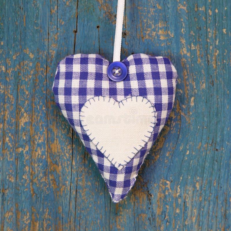 Forma fatta a mano del cuore contro superficie di legno blu. immagine stock
