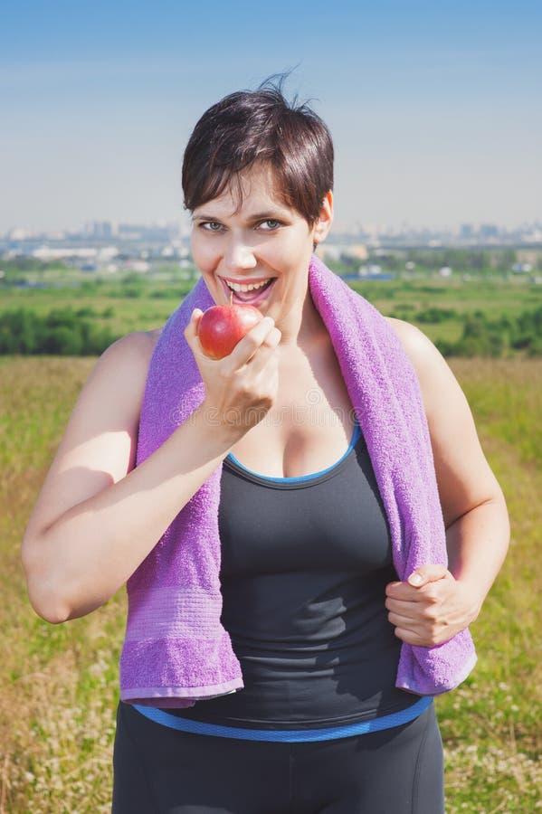Forma fisica bella più la donna di dimensione che mangia mela immagini stock