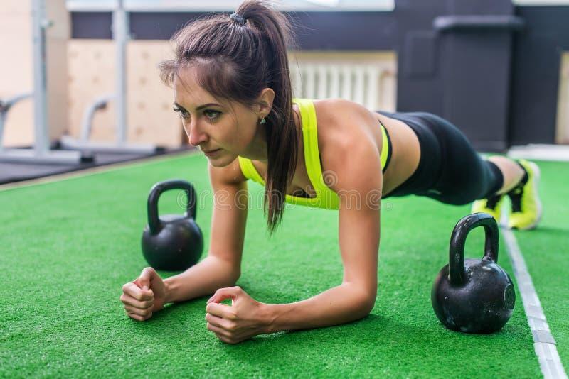 Forma fisica che prepara donna sportiva atletica che fa esercizio della plancia in palestra o concetto della classe di yoga che e fotografia stock libera da diritti