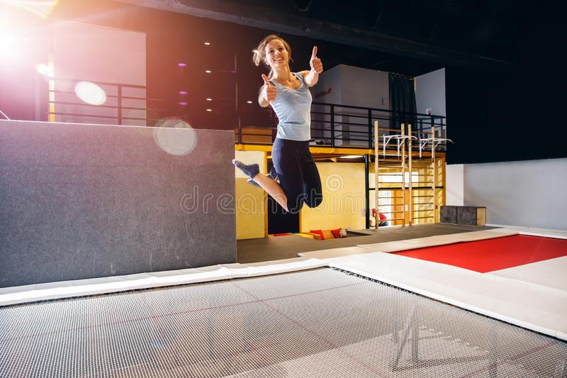 Forma fisica dello sportivo della giovane donna che salta sul trampolino del club fotografie stock libere da diritti