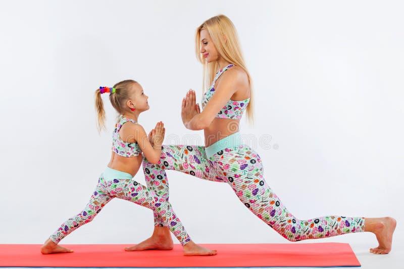 Forma fisica di yoga di Hatha Giovane esercizio della figlia e della madre insieme all'interno Sguardo della famiglia fotografia stock