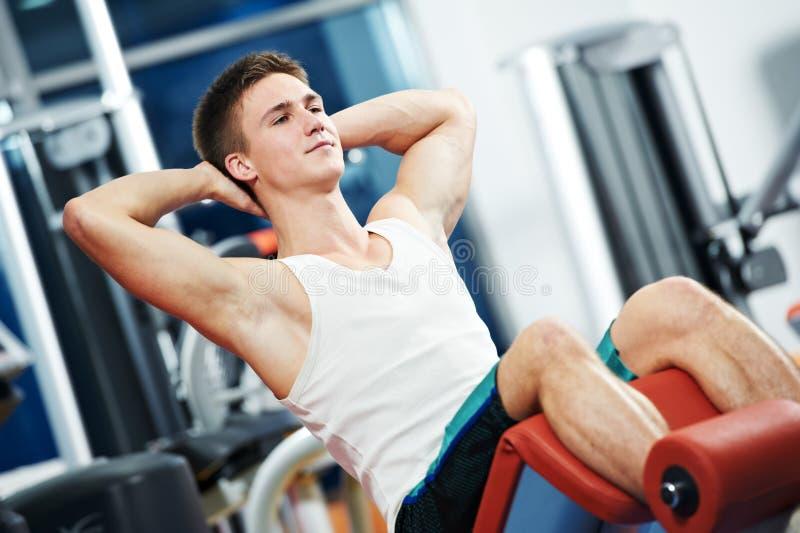 Forma fisica e sport uomo che fa gli esercizi dei muscoli addominali in palestra immagine stock libera da diritti