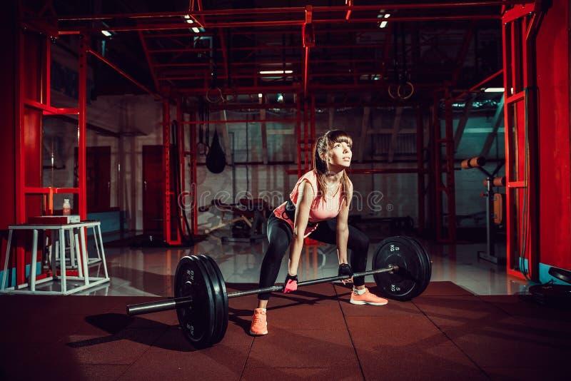 Forma fisica femminile che esegue facendo esercizio del deadlift con la barra del peso immagini stock