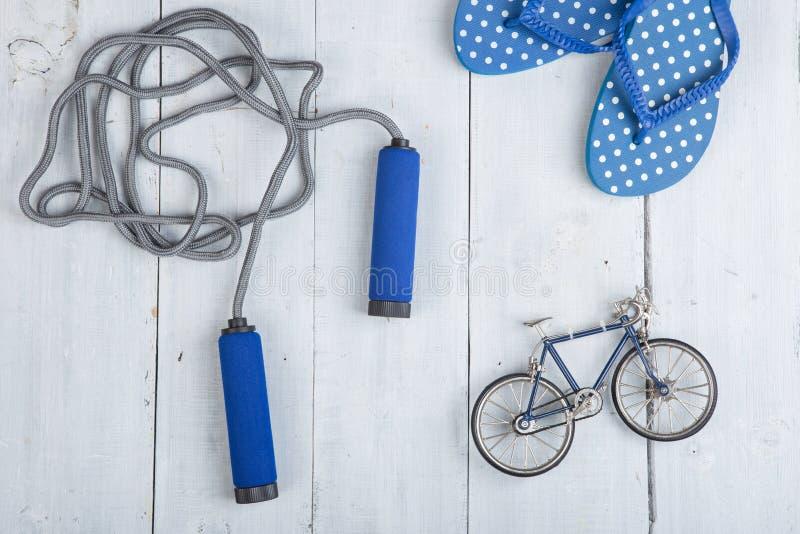 Forma fisica/sport e concetto sano di stile di vita - saltare/salto della corda con le maniglie blu, Flip-flop in pois e modello  immagini stock libere da diritti