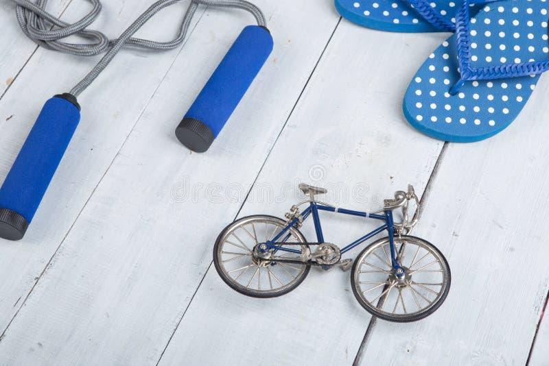 Forma fisica/sport e concetto sano di stile di vita - saltare/salto della corda con le maniglie blu, Flip-flop in pois e modello  immagini stock