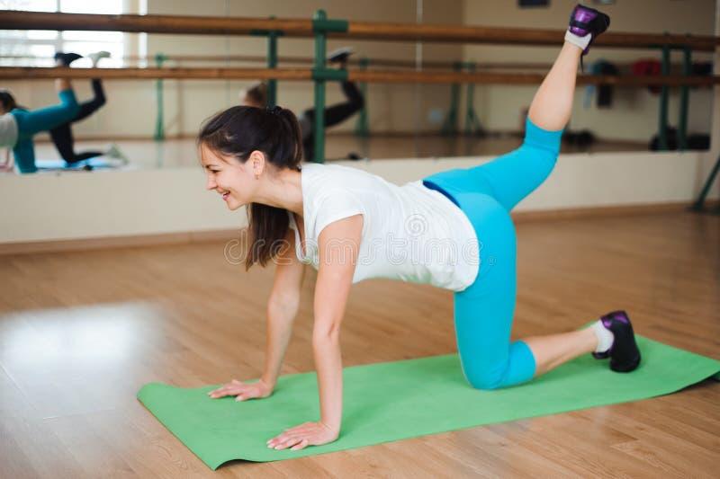 Forma fisica, sport, esercitante stile di vita - usura di donne felice in tute che fanno gli esercizi alla palestra fotografie stock
