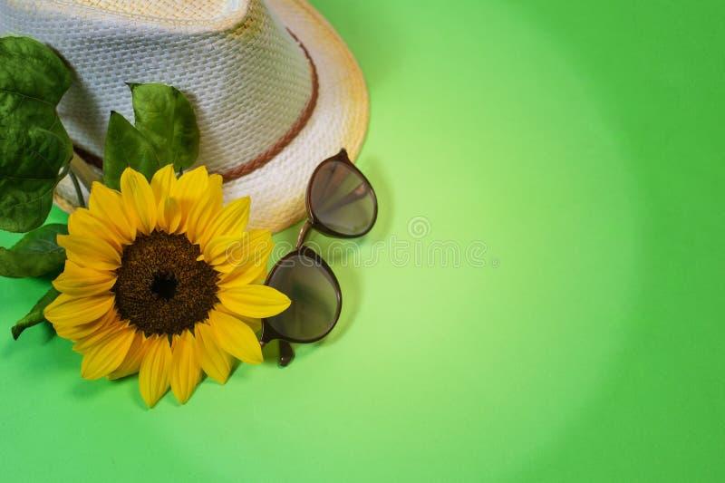 Forma flatlay com óculos de sol, chapéu do barqueiro da palha e o girassol amarelo grande brilhante fotografia de stock royalty free