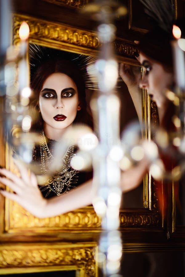 Forma gótico: jovem mulher bonita misteriosa que olha no espelho fotos de stock royalty free
