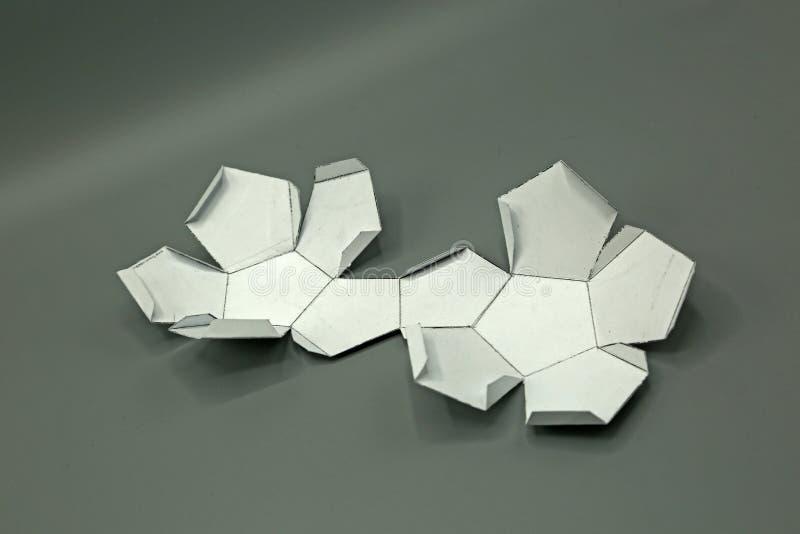 Forma geometrica tagliata di carta e fotografata su fondo grigio dodecahedron 2d forma pieghevole formare una forma 3d o un solid fotografia stock