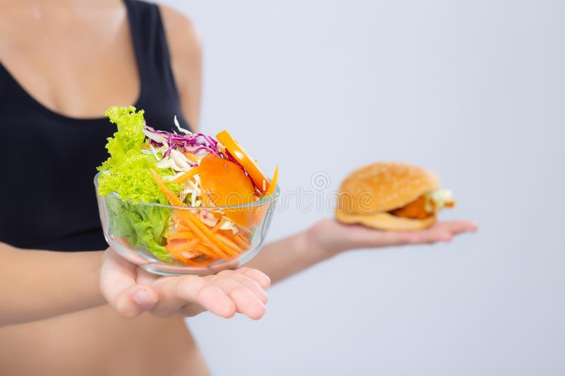 Forma magro da mulher asiática do close up com a dieta que escolhe o vegetal de salada fresco e o Hamburger isolados no fundo bra fotos de stock
