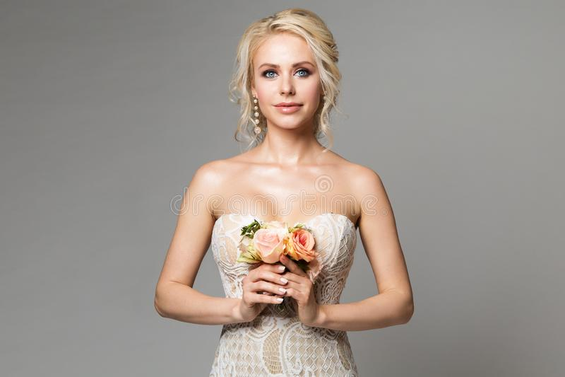 A forma modela o retrato da beleza com ramalhete das flores, a composição bonita da mulher e o penteado, tiro do estúdio da menin imagem de stock