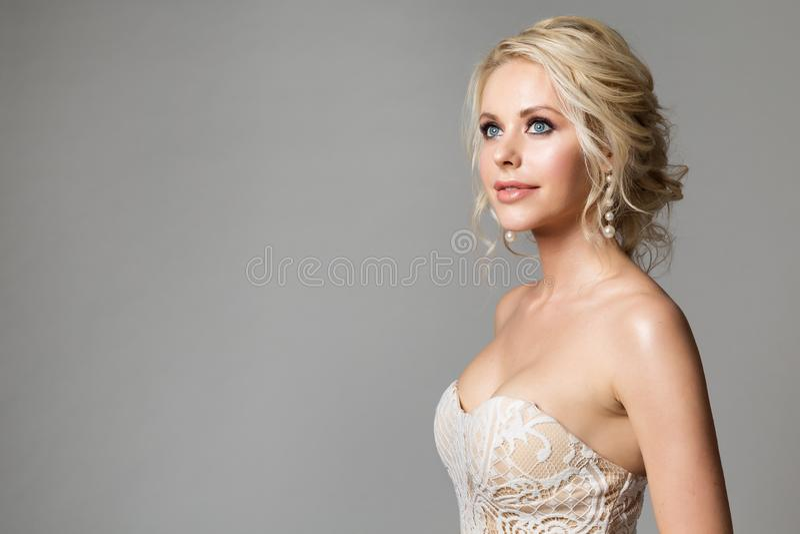 A forma modela o retrato da beleza, a composição bonita da mulher e o penteado, tiro do estúdio da noiva no cinza fotos de stock royalty free