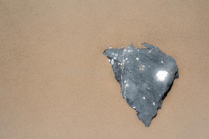 Forma nera del cuore della roccia su effetto di incandescenza della sabbia immagini stock libere da diritti