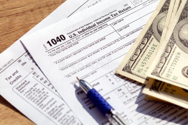 Forma, penna e banconote in dollari di imposta degli Stati Uniti 1040 Concetto del rimborso di imposta immagini stock libere da diritti