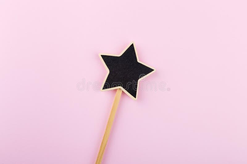 Forma preta da estrela do quadro em uma vara de madeira Copie o espaço foto de stock royalty free