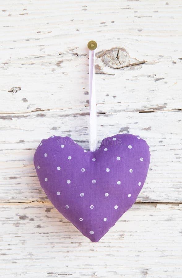 Forma punteggiata romantica del cuore che appende sopra la superficie di legno bianca o immagine stock libera da diritti