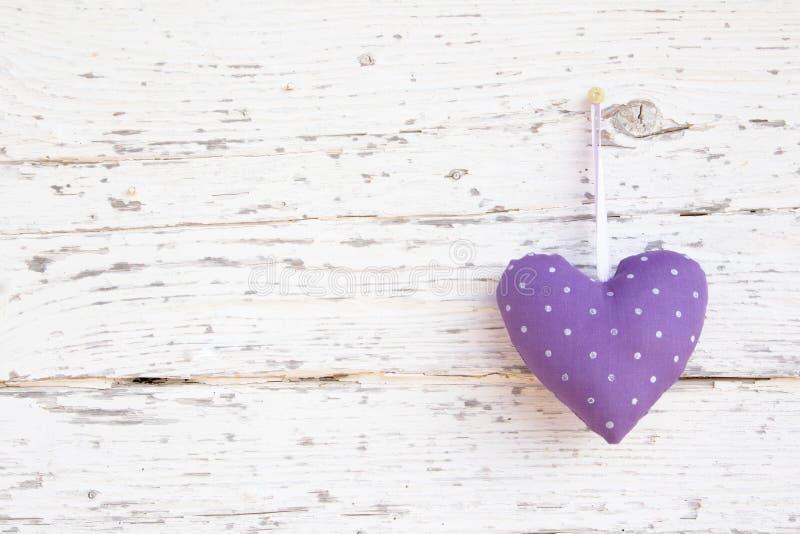 Forma punteggiata romantica del cuore che appende sopra la superficie di legno bianca o fotografia stock libera da diritti