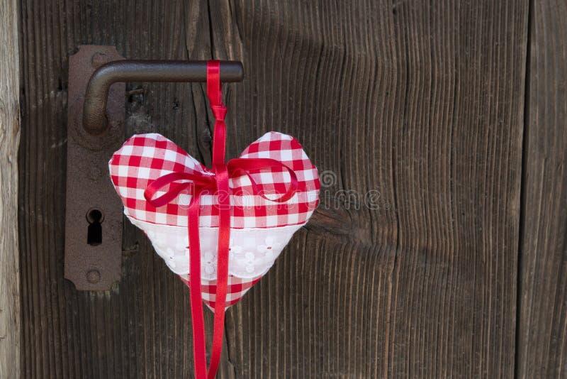 Forma a quadretti del cuore che appende sulla maniglia di porta arrugginita per il biglietto di S. Valentino immagine stock libera da diritti