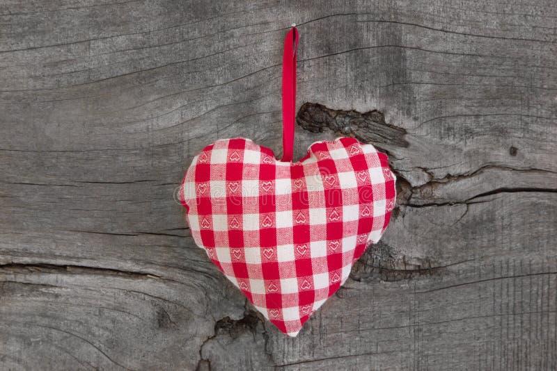 Forma a quadretti rossa del cuore che appende su un fondo di legno per val immagine stock libera da diritti