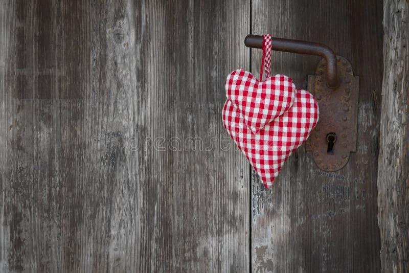 Forma a quadretti rossa del cuore due che appende sulla maniglia di porta arrugginita per la v fotografie stock