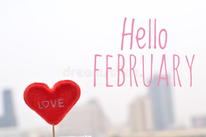 Forma roja del corazón con hola el texto de febrero en fondo de la opinión de la ciudad fotografía de archivo