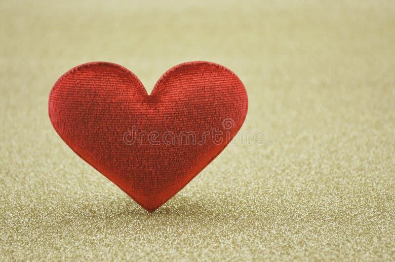 Forma roja del corazón de la tela en fondo del oro foto de archivo