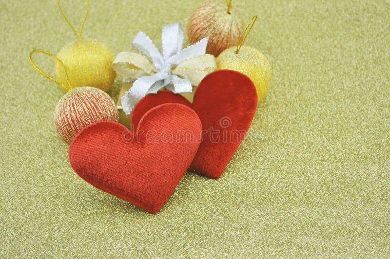 Forma roja del corazón del amor de la tela con la caja de regalo en el fondo del oro, Lo imagen de archivo