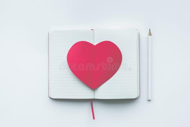 Forma roja del corazón en el fondo blanco de la libreta amor, tarjeta del día de San Valentín fotos de archivo libres de regalías
