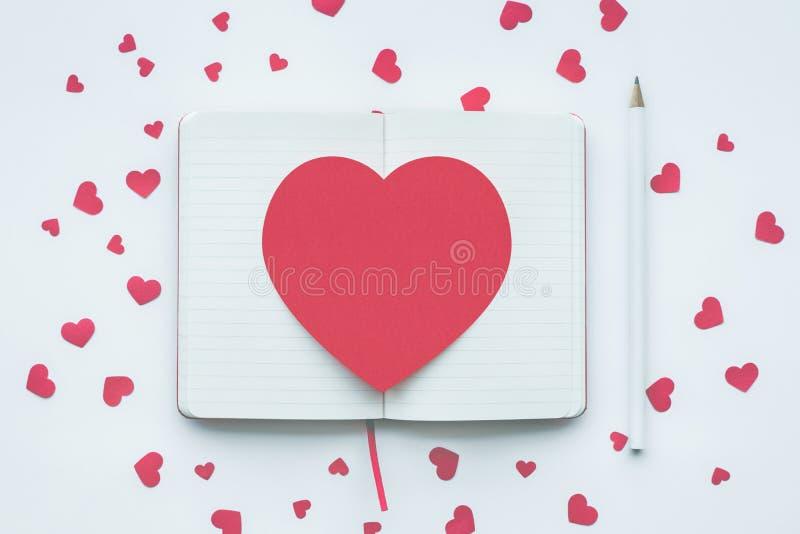 Forma roja del corazón en el fondo blanco de la libreta amor, tarjeta del día de San Valentín foto de archivo