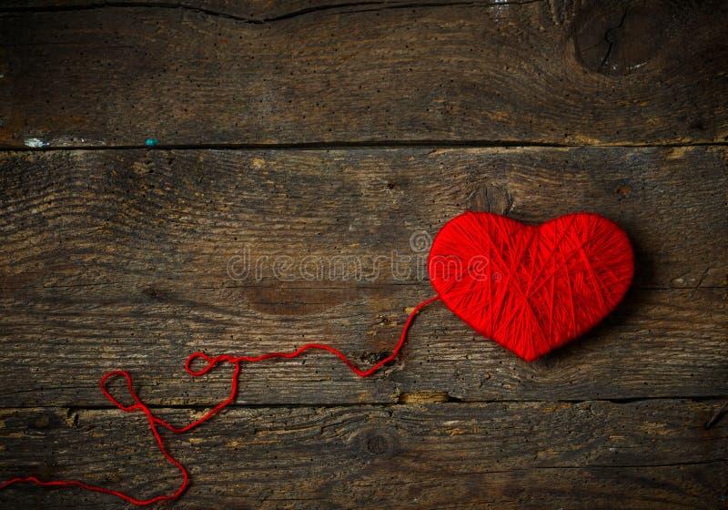 Forma roja del corazón hecha de las lanas en viejo fondo de madera lamentable imagen de archivo