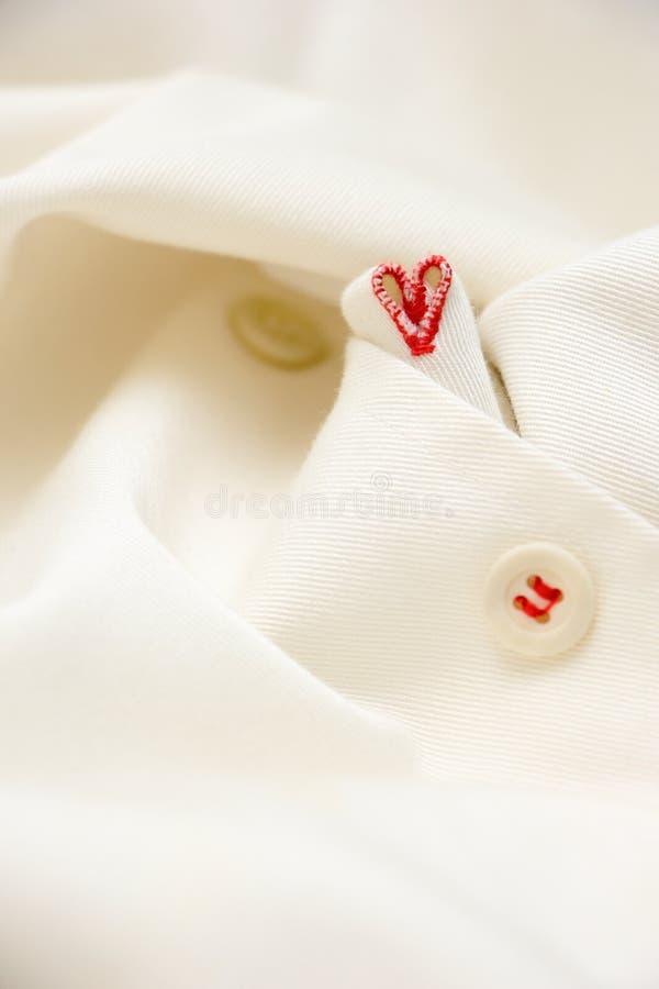 forma rossa del cuore con il punto di occhiello ed il fondo febric bianco immagini stock
