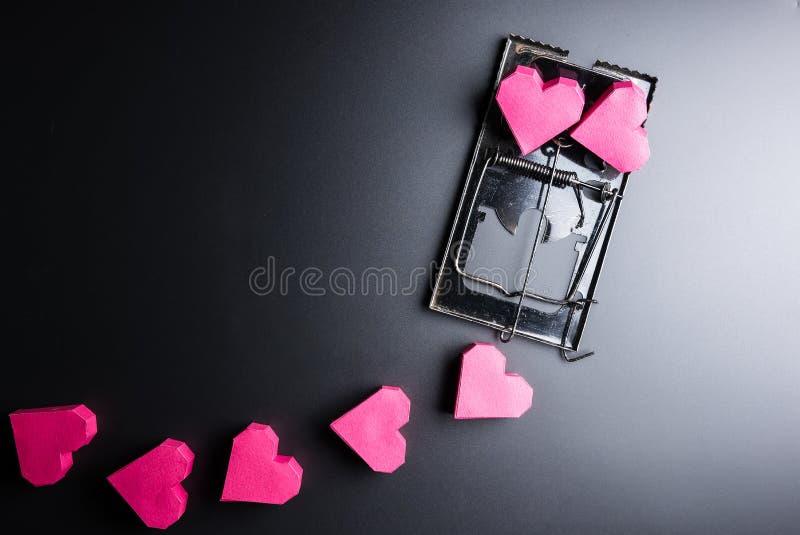 Forma rossa del cuore della scatola di uso della trappola per topi come esca sui wi neri del fondo immagine stock libera da diritti