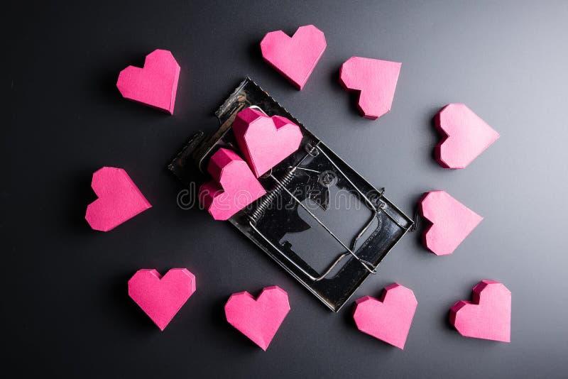 Forma rossa del cuore della scatola di uso della trappola per topi come esca sui wi neri del fondo fotografia stock