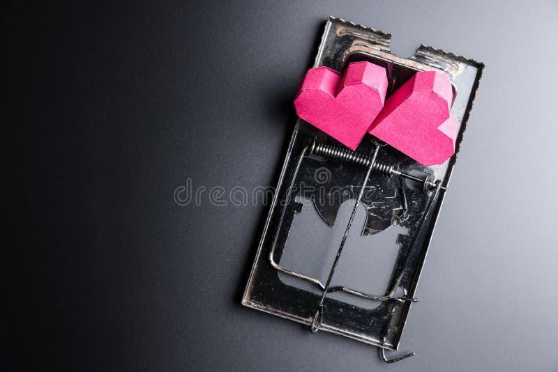 Forma rossa del cuore della scatola di uso della trappola per topi come esca sui wi neri del fondo fotografie stock libere da diritti