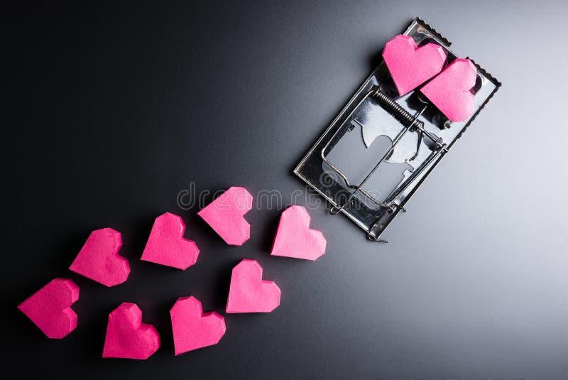 Forma rossa del cuore della scatola di uso della trappola per topi come esca sui wi neri del fondo immagini stock libere da diritti