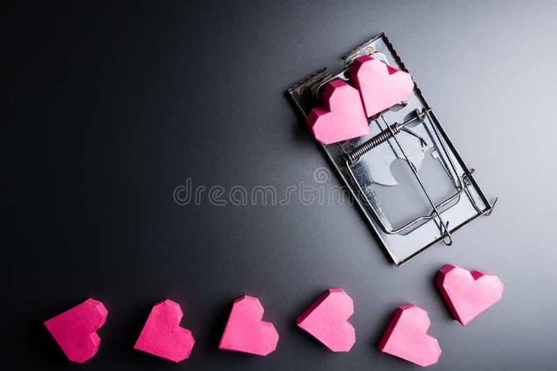 Forma rossa del cuore della scatola di uso della trappola per topi come esca sui wi neri del fondo immagini stock